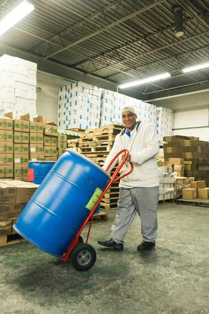 Happy injured worker pushing barrel after completing retraining program Separovic Injury Lawyers
